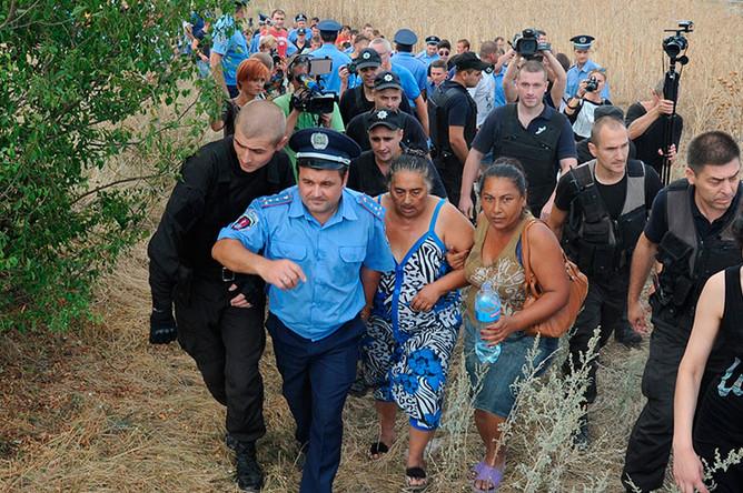 Сотрудники правоохранительных органов успокаивают жителей села Лощиновка в Одесской области, где произошли столкновения и погромы домов цыган после убийства ребенка