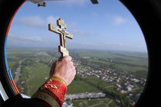 Священник Симферопольской и Крымской епархии отец Василий с вертолета МИ-8 МЧС России освящает крымскую землю