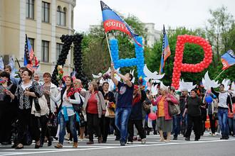 Участники праздничного шествия, приуроченного к годовщине референдума о самоопределении ДНР и ЛНР