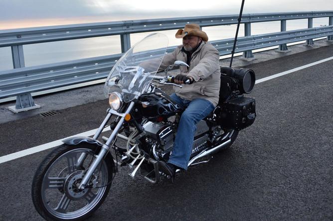 Мотоциклист едет по автодорожной части Крымского моста