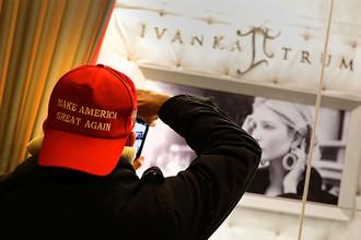 Мужчина в кепке с предвыборным лозунгом Дональда Трампа около витрины ювелирного магазина Иванки Трамп в Нью-Йорке, декабрь 2016 года