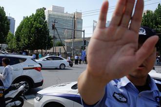 Полицейский на месте взрыва около посольства США в Пекине, 26 июля 2018 года