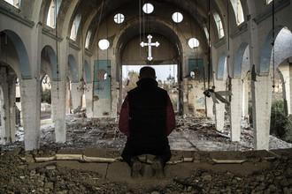 Житель одной из деревень в провинции Эль-Хасаке на северо-востоке Сирии молится в храме Святого Георгия, уничтоженного боевиками ИГ