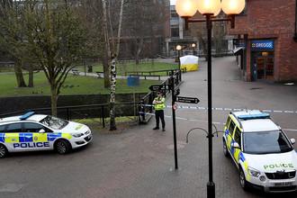 Полицейское оцепление около торгового центра в британском Солсбери после инцидента с бывшим российским разведчиком Сергеем Скрипалем, 6 марта 2018 года. Тент накрывает скамейку, где мужчина и его дочь были найдены в критическом состоянии