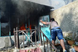 Мужчина тушит пожар в жилом секторе Ростова-на-Дону, 21 августа 2017 года