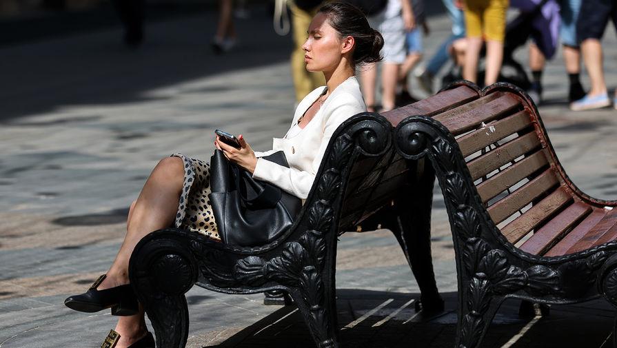 Девушка отдыхает под солнцем на Никольской улице в Москве, 18 мая 2021 года