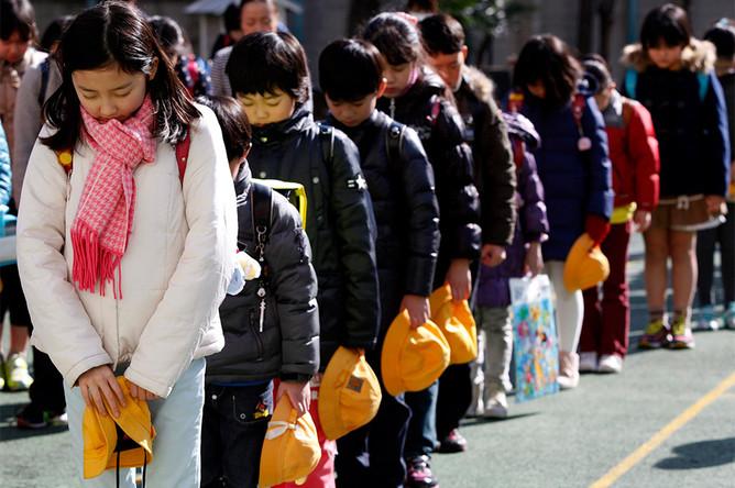 Школьники во время траурных мероприятий, приуроченных к третьей годовщине землетрясения и цунами в Японии