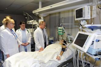 Президент России Владимир Путин (справа на дальнем плане) во время посещения российской спортсменки Марии Комиссаровой в краснополянской больнице №8