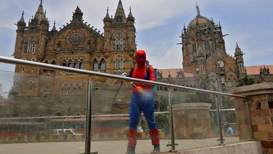 Мужчина в костюме Человека-паука во время дезинфекции ограждения около железнодорожной станции в Мумбаи, 21 апреля 2021 года