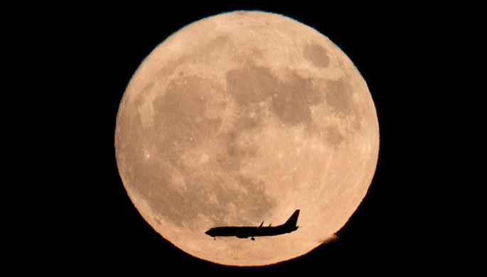 Самолет над суперлунием в Пекине, Китай