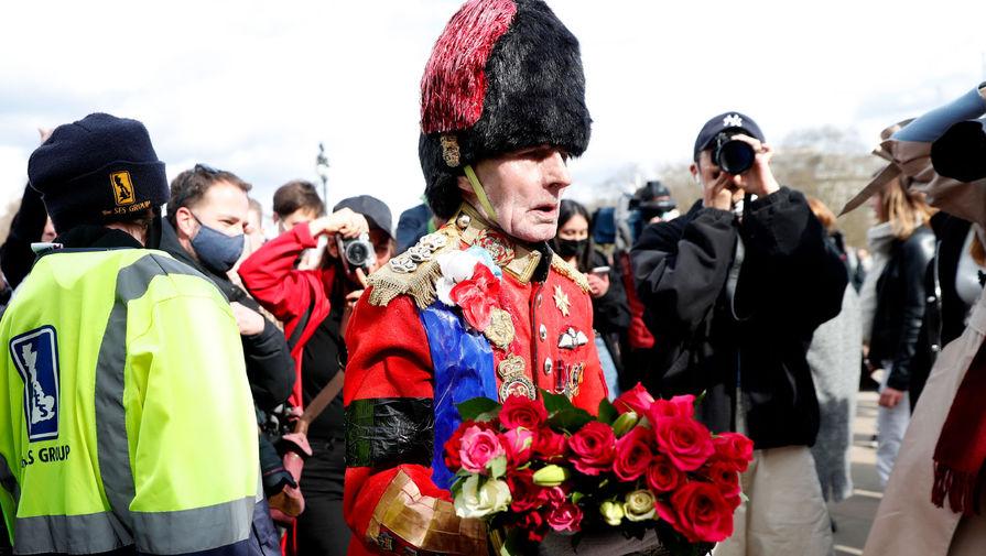 Британец в форме гвардейца королевы несет цветы к воротам Букингемского дворца в Лондоне в память о принце Филиппе, 9 апреля 2021 года