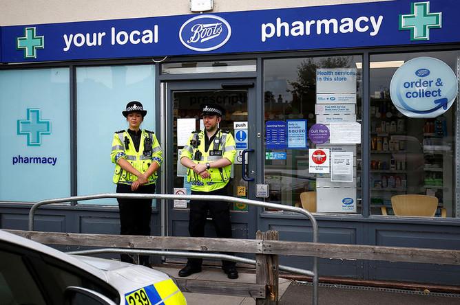 Сотрудники британской полиции около здания аптеки после инцидента с отравлением в Эймсбери, 4 июля 2018 года