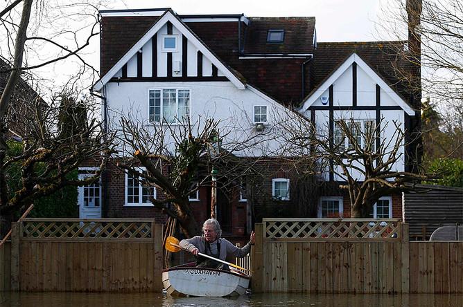 Житель городка Рейсбери покидает свой затопленный дом на лодке на юге Англии