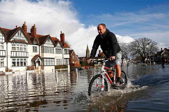 Житель населенного пункта Дэтчет едет по затопленной улице на велосипеде на юге Англии