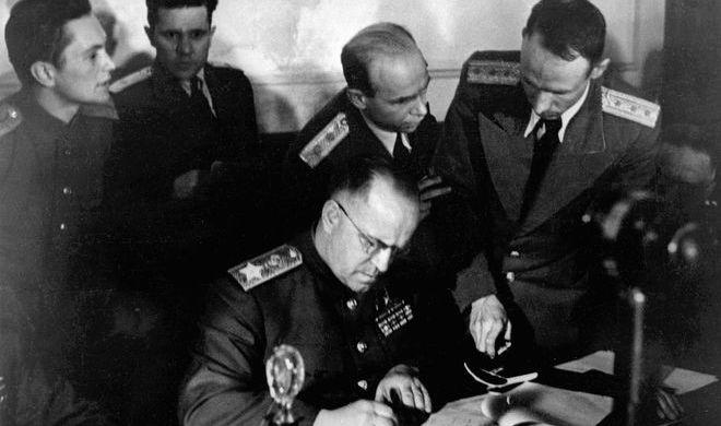 Заместитель Верховного Главнокомандующего Маршал Советского Союза Георгий Константинович Жуков (в центре) подписывает Акт о безоговорочной капитуляции фашистской Германии в Карлсхорсте, 8 мая 1945 года.