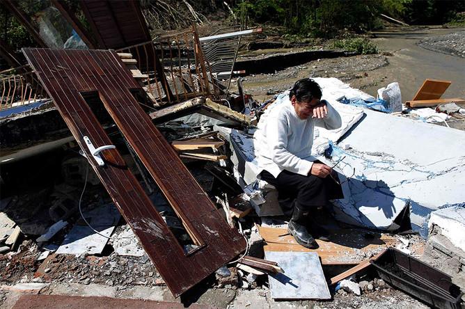 Женщина плачет у разрушенного в результате наводнения дома в сербской деревне Крупань на западе от Белграда