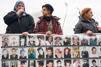 Женщины с плакатом с изображениями жертв во время процесса над сербским генералом Ратко Младичем в Международном трибунале по бывшей Югославии в Гааге, 22 ноября 2017 год