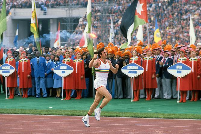 Трехкратный олимпийский чемпион Виктор Санеев вносит факел олимпийского огня на стадион