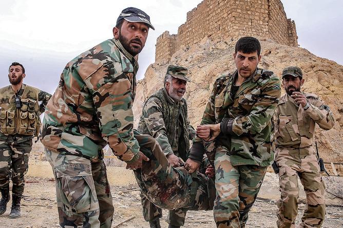 Бойцы сирийской армии несут раненого у подножия замка Фахр ад-Дина
