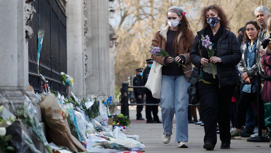 Британцы несут цветы к воротам Букингемского дворца в Лондоне после объявления о смерти принца Филиппа, 9 апреля 2021 года