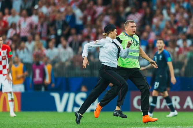 Участники группы Pussy Riot выбегают на поле во время финального матча чемпионата мира по футболу между сборными Франции и Хорватии, 15 июля 2018 года