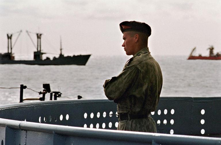 Российский моряк на борту ракетного крейсера «Петр Великий» во время спасательной операции на месте крушения АПЛ «Курск» в Баренцевом море, 21 августа 2000 года. На заднем плане российское судно «Михаил Рудницкий» и норвежское Normand Pioneer