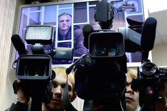 Фотограф Денис Синяков (на экране), обвиняемый в незаконной попытке проникновения на платформу «Приразломная», во время рассмотрения апелляции