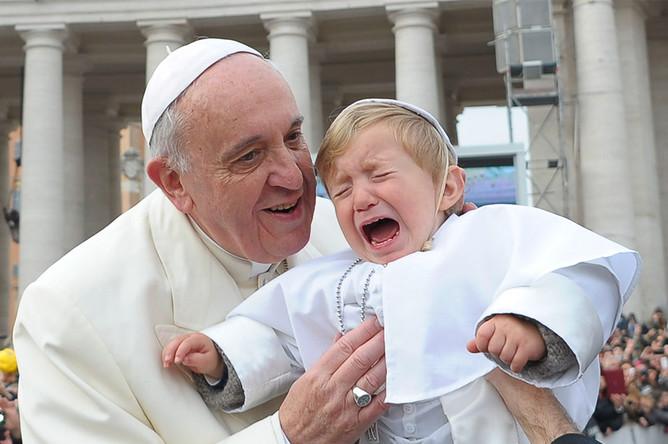 Папа Римский Франциск благословляет ребенка на площади Святого Петра в Ватикане