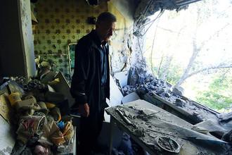 Мужчина в квартире, пострадавшей в результате обстрелов поселка Октябрьский Куйбышевского района