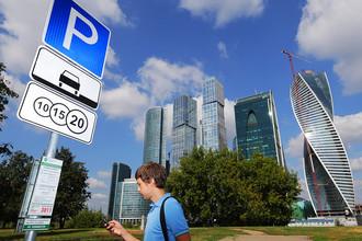 Житель города во время оплаты парковки с помощью мобильного телефона на платной парковке