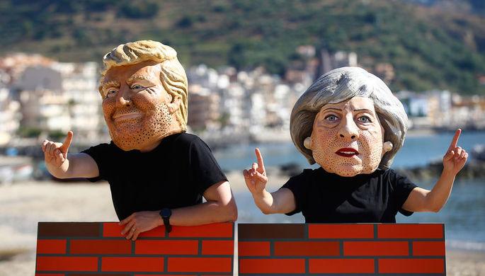 Протестующие в масках с изображением президента США Дональда Трампа и британского премьера Терезы...