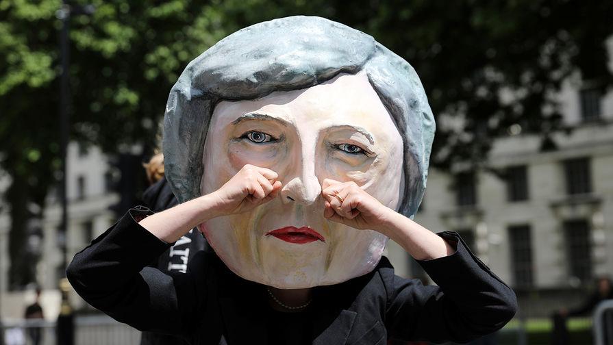 Протестующий в маске британского премьера Терезы Мэй в Лондоне, июнь 2017 года