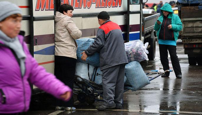 Торговцы у междугороднего автобуса на территории торгового центра «Садовод» в Москве.