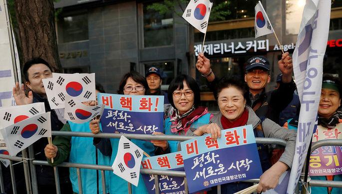 Жители Южной Кореи приветствуют президента страны перед его встречей с Ким Чен Ыном, 27 апреля 2018...
