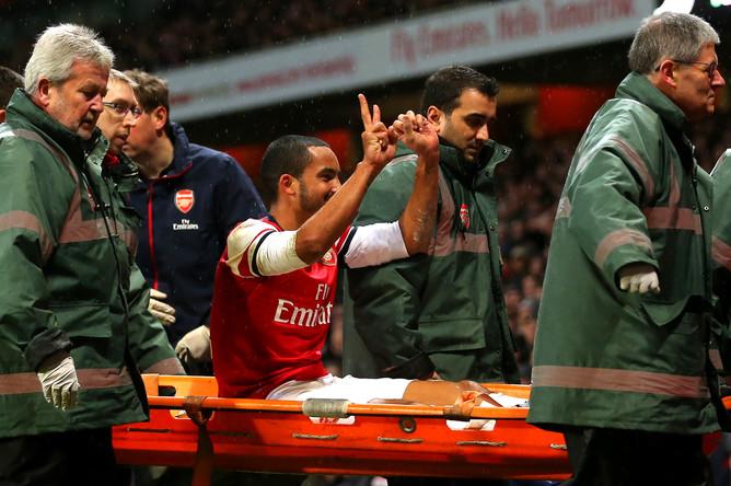 Получивший травму форвард «Арсенала» Тео Уолкотт демонстрирует фанатам итоговый счет матча против «Тоттенхэма»