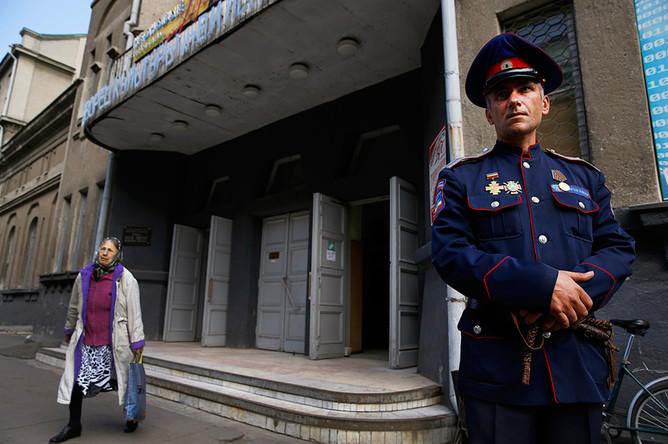Офицер гражданской обороны стоит на страже у избирательного участка во время референдума в Славянске