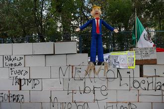 Импровизированная стена и пиньята в виде президента США Дональда Трампа во время протеста около американского посольства в Мехико, 20 января 2017 года