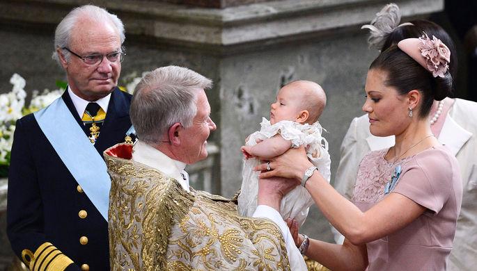 Король Швеции Карл XVI Густав, архиепископ Андерс Вейрюд и кронпринцесса Виктория с дочерью Эстель во время торжественной церемонии в Стокгольме, 2012 год