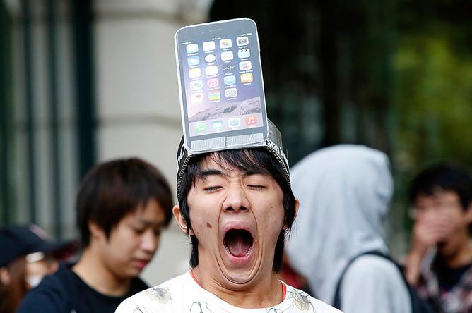 Мужчина с макетом модели iPhone 6 Plus на голове стоит в очереди токийского Apple Store