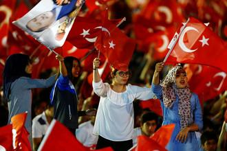Турецкие флаги и портрет президента Реджепа Тайипа Эрдогана на демонстрации перед зданием парламента Турции в Анкаре в годовщину попытки госпереворота, 16 июля 2017 года