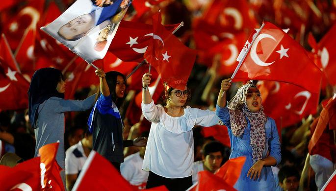 Турецкие флаги и портрет президента Реджепа Тайипа Эрдогана на демонстрации перед зданием парламента...