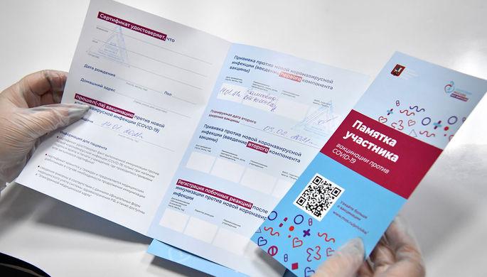 Медработник с сертификатами о вакцинации от новой коронавирусной инфекции COVID-19 и памяткой участнику вакцинации, которые выдаются пациентам после вакцинации вакциной «Спутник V» в прививочном пункте
