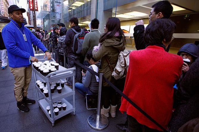 Сотрудник Apple Store предлагает кофе покупателям, ожидающим своего iPhone 6, в Сиднее