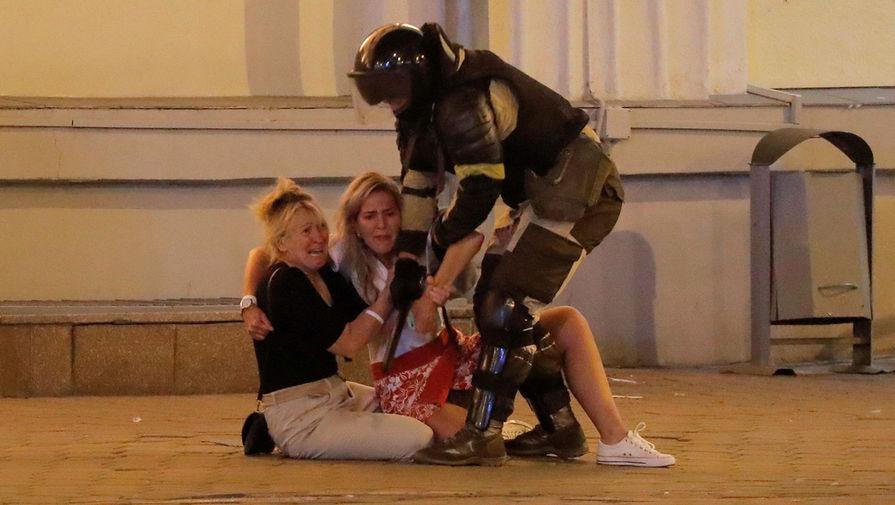 Сотрудник спецназа задерживает участниц акций протеста в Минске во вторую ночь после выборов президента Белоруссии, 10 августа 2020 года