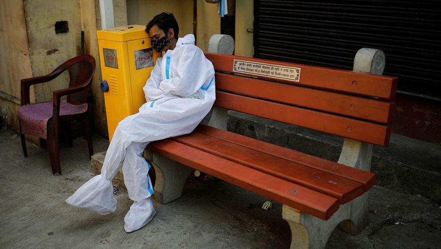 Медицинский работник около крематория в Нью-Дели, 21 апреля 2021 года
