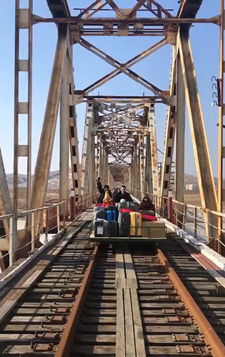 Сотрудники российского посольства в КНДР и члены их семей идут по путям к российской границе, 25 февраля 2021 года