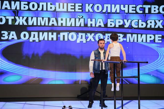 Зелим Куриев и его шестилетний сын Рахим Куриев во время регистрации рекорда по отжиманиям на брусьях в Книге рекордов России в студии телерадиокомпании «Грозный», 20 марта 2019 года