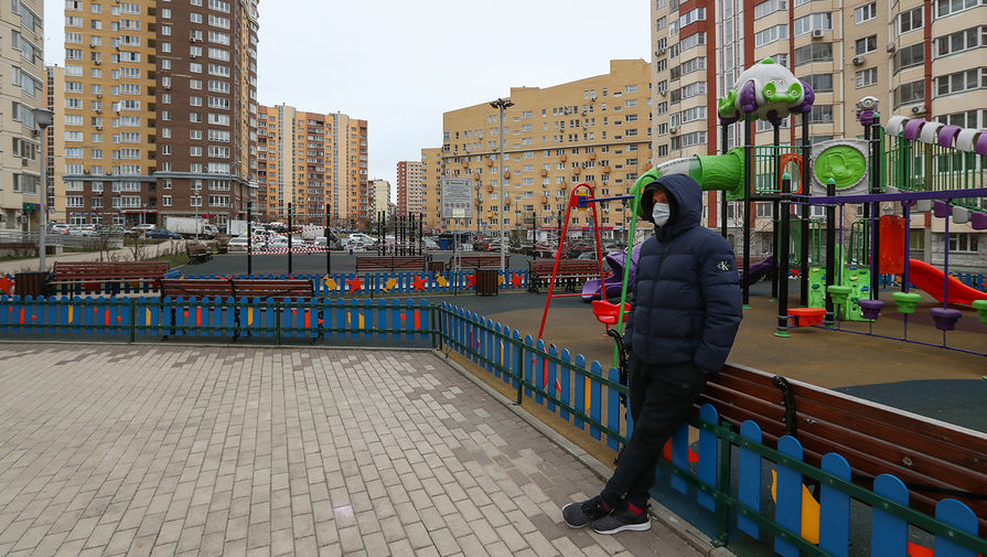 Мужчина в медицинской маске на детской площадке во дворе поселка Коммунарка, 30 марта 2020 года