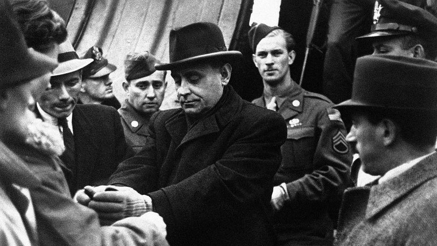 Венгерский полицейский надевает наручники на Ференца Салаши при выходе из самолета в аэропорту Будапешта, 5 октября 1945 года