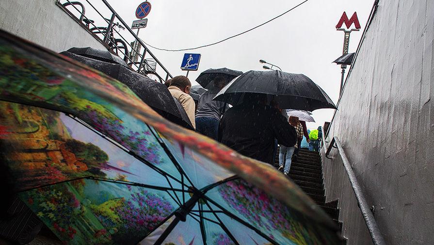 Люди выходят из подземного перехода Московского метрополитена во время дождя в Москве